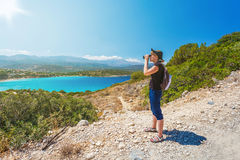 Traveling girl watching with binoculars on the sea background Royalty Free Stock Photos