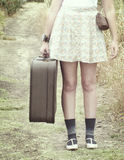 Traveling Girl. A girl or woman with a suitcase traveling up a field dirt path Stock Image