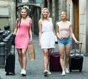Traveling girls walking with suitcases in city. Group of young smiling traveling girls taking promenade with suitcases in summer city Stock Images