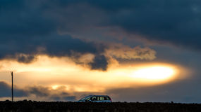 Car with Stormy clouds during sunset Royalty Free Stock Images