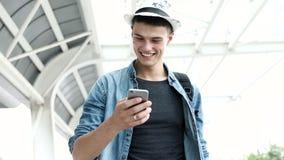 traveling Hombre sonriente con equipaje usando el teléfono móvil almacen de metraje de vídeo
