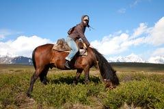Traveling on horseback. Young woman tourist, traveling on horseback Royalty Free Stock Image