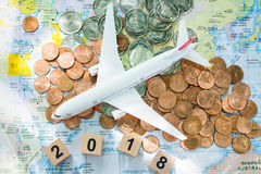 Traveling, journey, travel to destination background concept. Airplane figure on a world map and a pile of coins and wooden numbers 2018 using as traveling Royalty Free Stock Photo