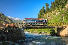 Picturesque Pahalgam. Traveling in Kashmir. A local bus crosses a bridge constructed over Lidder river in picturesque Pahalgam, Kashmir, India Royalty Free Stock Photo