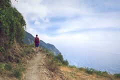 Traveling but keeping distance. Hiker high up in the mountains in Cinque Terre  Liguria  Italy.