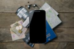 Traveling light concept - everything you need is in your phone. Modern technology. Phone in front of passport, map, camera, money Stock Photos