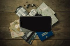 Traveling light concept - everything you need is in your phone. Modern technology. Phone in front of passport, map, camera, money Stock Photography