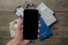 Traveling light concept - everything you need is in your phone. Modern technology. Hand holding phone in front of passport, map, camera, money Stock Images