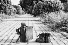 Traveling light! Worn boots, suitcase, film camera, brick road. Black-and-white. Traveling light! Worn ankle boots next to a vintage cardboard suitcase, a film Royalty Free Stock Photography