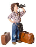 Traveling little boy with old suitcases. Looking to spyglass, isolated on white Stock Image