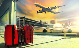 Traveling luggage in airport terminal building and jet plane fly. Ing over urban scene royalty free stock photos