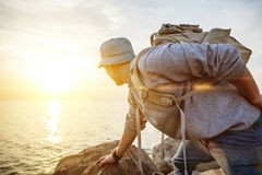 Traveling man with backpack near the ocean looking far away Stock Photography