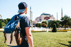 A traveling man with a backpack in Sultanahmet Square near the famous Aya Sofia mosque in Istanbul in Turkey. Travel Stock Image