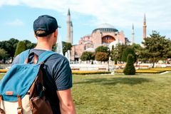 A traveling man with a backpack in Sultanahmet Square near the famous Aya Sofia mosque in Istanbul in Turkey. Travel. Sightseeing Stock Photo