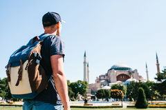 A traveling man with a backpack in Sultanahmet Square near the famous Aya Sofia mosque in Istanbul in Turkey. Travel Royalty Free Stock Photo