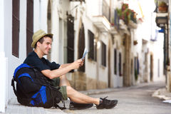 Traveling man sitting on sidewalk with bag looking at map Royalty Free Stock Images