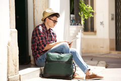 Traveling man sitting on sidewalk reading map. Side portrait of a handsome young traveling man sitting on sidewalk reading map Royalty Free Stock Photos