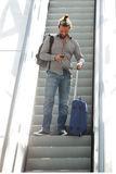 Traveling man standing on escalator looking at mobile phone. Portrait of traveling man standing on escalator with luggage looking at mobile phone Royalty Free Stock Photos