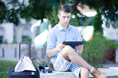 Tourist reading tablet. A young man reads a tablet while traveling Royalty Free Stock Images