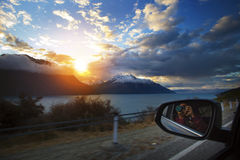 Traveling man taking sunset photography while car driving on cou Stock Photos