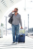 Traveling man walking with mobile phone and luggage. Full length portrait of traveling man walking with mobile phone and luggage Royalty Free Stock Photography