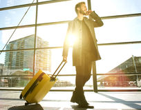 Traveling man walking and talking on mobile phone at airport. Side portrait of a handsome traveling man walking and talking on mobile phone at airport Royalty Free Stock Photo