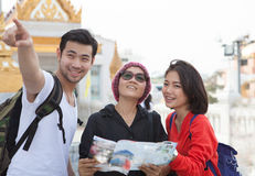 Traveling man woman and senior tourist holding travel guide book Stock Photo