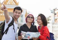 Traveling man woman and senior tourist holding travel guide book. Traveling men women and senior tourist holding travel guide book in hand pointing to Stock Photo