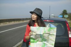 Traveling with a map on the road. Girl is traveling with a map on the road, conceptual photo stock photo