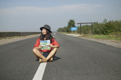 Traveling with a map on the road. Girl is traveling with a map on the road, conceptual photo royalty free stock photo