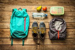 Traveling - packing preparing for adventure trip concept. Traveling - packing preparing for adventure school trip concept. Backpack, boots, jacket, lunch box Royalty Free Stock Image