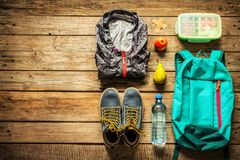 Traveling - packing preparing for adventure trip concept. Traveling - packing preparing for adventure school trip concept. Backpack, boots, jacket, lunch box Stock Image