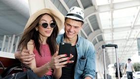 traveling Pares usando el teléfono, transporte que espera cerca del aeropuerto almacen de video