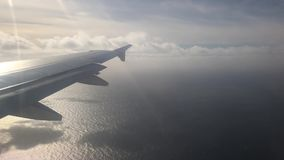 Traveling in plane. Sea surface, plane wing, sunshine and clouds stock video footage