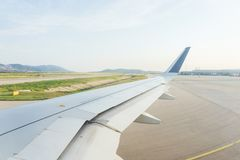 Traveling by plane. View from the window to the clouds and dawn. Part of the wing of the airliner and the airport runway from the porthole. Passenger airplane stock image