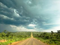 Traveling on road in africa with dark clouds on the horizon. Traveling in Angola. Tar road in centre, lush green flora on sides and dark blue clouds indicating stock photography