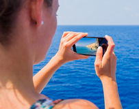 Traveling through seas and oceans. Beautiful girl photographing landscapes while traveling with ship Stock Photos