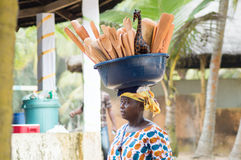 Traveling shopping. Abidjan, Cote d'Ivoire-August 29, 2015: a traveling shopping, bowl on her head filled with art , walks to the beach for sale Royalty Free Stock Image