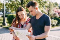 Couple lost in city, looking at map. Traveling, sightseeing, city tour, vacation, adventure, holiday Couple lost in city looking at map Royalty Free Stock Photo