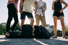 Friends with backpacks searching the location. Traveling, sightseeing, group travel, city tour, student exchange program, togetherness. Four young friends with Royalty Free Stock Images