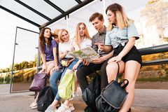 Tourists searching the location on city map. Traveling, sightseeing, group travel, city tour, togetherness. Tired tourists rest at bus stop searching the royalty free stock images