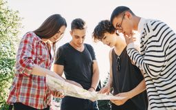 Friends searching the location on touristic map. Traveling, sightseeing, group travel, togetherness. Group of friends searching the location on touristic map Royalty Free Stock Images