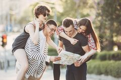 Friends searching the location on map. Traveling, sightseeing, vacation, holidays, adventure, friendship, togetherness. Friends searching the location on map Stock Photos
