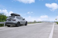 Traveling SUV car with roof box on highway against blue sky.  Royalty Free Stock Images