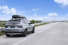 Traveling SUV car with roof box on highway against blue sky.  Stock Photo