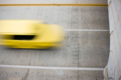 Traveling Taxi. Yellow taxi blur speeding traveling fast down a cement street Royalty Free Stock Image
