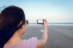 Traveling and Technology Concept, Woman is Taking Photos at The Beach by Her Smartphone in Summer Vacation. Asian Tourist is stock images