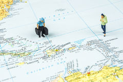 Traveling to the Caribbean. Closeup of miniature figurine of young travelers standing on big map next to Caribbean islands stock photography