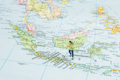 Traveling to Indonesia, Bali. Closeup of miniature figurine of young traveler standing on big map next to Indonesia, Bali island stock photography