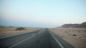 Traveling to Kairo. EGYPT - APRIL 28: Driving on empty road by the sea in desert stock footage